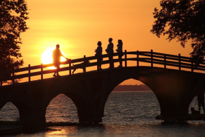 People crossing bridge at sunset